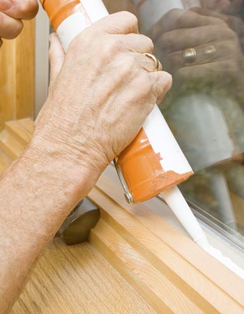A person caulks a window seal