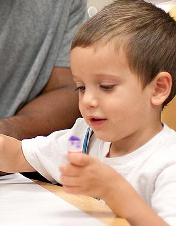 A young child uses creative supplies in a classroom