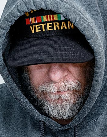 A bearded man wears a veteran hat under a sweatshirt hood