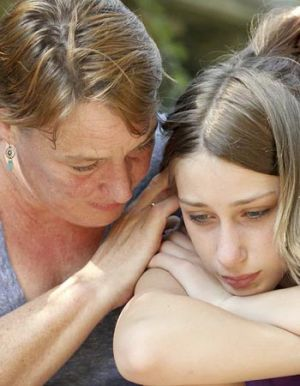 A mother consoles her teenage daughter