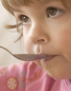 A young child feeds herself with a spoon